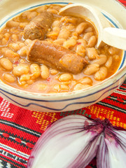 Fototapete - traditional cuisine beans with sausage and red onion