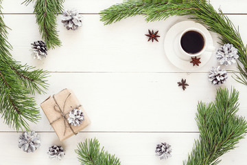 Cup of coffee, Christmas gift pine cones and branches on white w