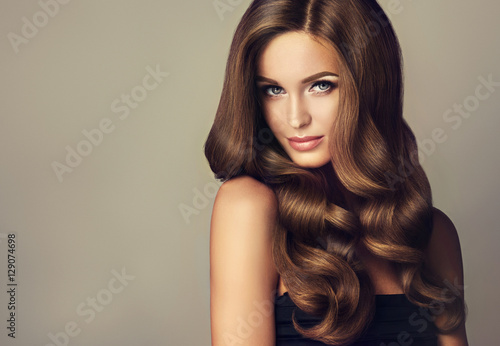 Wall mural Beautiful model girl with long wavy and shiny hair . Brunette woman with curly hairstyle