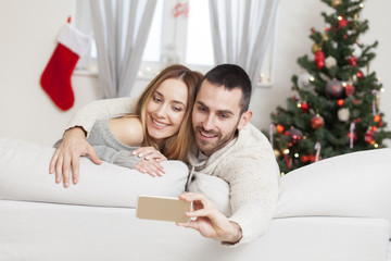 Young couple in love taking selfie on Christmas night