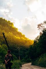 Guy admires the colorful sunset sky in Svaneti, Caucasus, Georgia