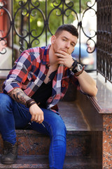 Young tattooed man posing on stairs, outdoor