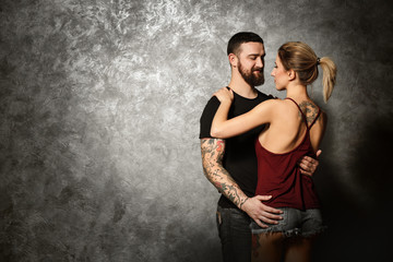 Portrait of young tattooed couple on gray wall background