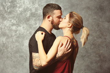 Portrait of kissing tattooed couple on gray wall background