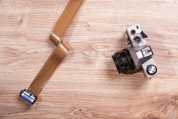 Old photo camera and film, exposure meter and retro analog camera on wood background.
