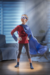 Little boy dressed as super hero in his living room