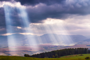 Sunlight beams over clouds in mountains. Rays in cloudy sky