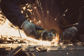 Man sawing metal with a rotary angle grinder on an aluminium surface and generating sparks