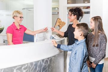 Kinder mit Mutter am Empfang beim Zahnarzt