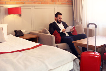Young businessman sitting in hotel room with tablet