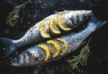 Sea bass fish with lemon on blackboard. Preparing for grill