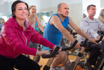 mature males and females on exercise bikes in the gym