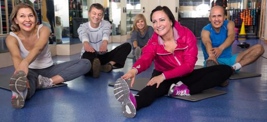 elderly people doing exercise on mat in modern gym