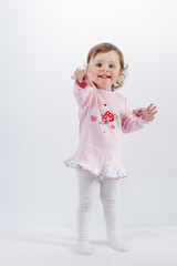 Charming baby in rose dress pointing at camera smiling