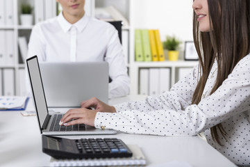 Two female colleagues are working in a white office at their lap