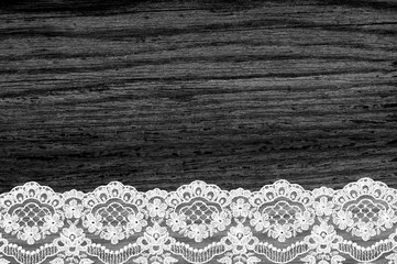 Black wood texture with white lace close-up as background