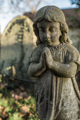 Statue of praying  child in graveyard