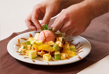 chef decorating fruit salad with ice-cream
