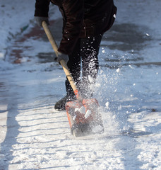 working woman cleans snow shovel in the nature