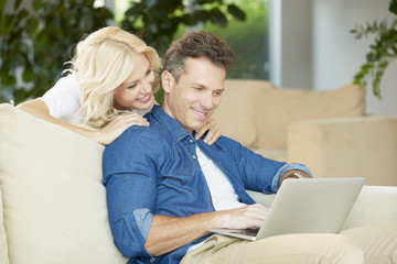 Portrait of middle aged couple sitting with a laptop at home. Beautiful blond woman using laptop while handsome man sitting next to her and enjoy surfing on internet.