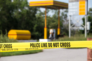 police line do no cross with gas station background in crime scene
