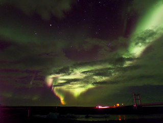Amazing green and pink Aurora Borealis flashing on the cloudy sky over the bridge and glacier lagoon in south Iceland