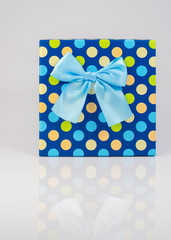 Blue gift box polka dots and blue ribbon isolated on white background
