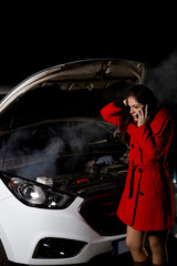 young girl frustrated waiting for help beside broken car with open hood and smoke at night