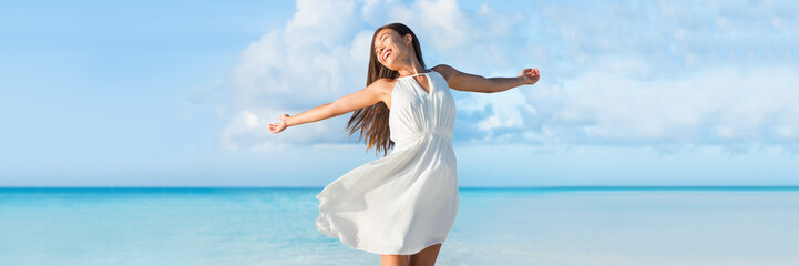 Wall Mural - Freedom young woman with arms up outstretched to the sky with blue ocean landscape beach background copy space. Banner panorama. Asian girl in white dress dancing carefree in sunset.