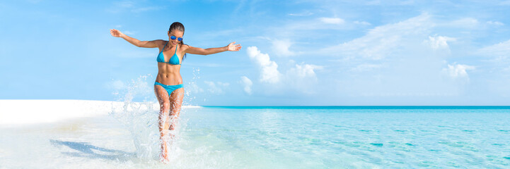 Sexy bikini body woman playful on paradise tropical beach having fun playing splashing water in freedom with open arms. Beautiful fit body girl on travel vacation. Banner crop for copyspace.