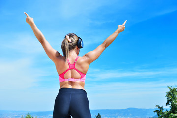 Success fitness winning woman concept with earphones.