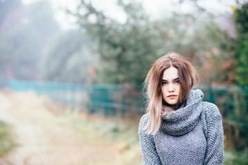 Pensive beautiful young woman in woolen sweater