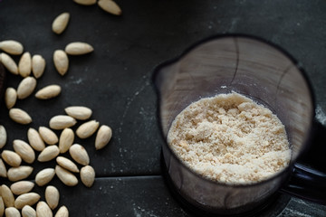 Grinding almond flour with bleached almonds in blender