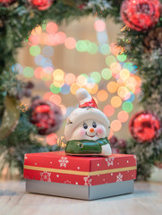 Christmas background. Small toy on top of a Christmas present box .In the background a Christmas Tree ornament and blurry coloured lights.