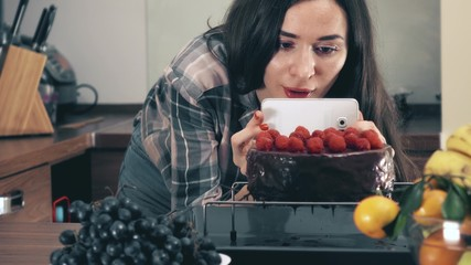 Brunette young woman making photos and videos of her raspberry cake with the smartphone. Amateur cooking, social media sharing concepts