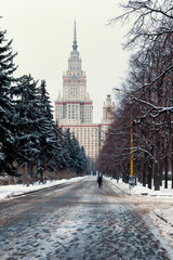 Track in the park leading to the Moscow State University building. Main building of the Lomonosov Moscow State University. MGU. The Sparrow Hills, Moscow, Russia. Winter.