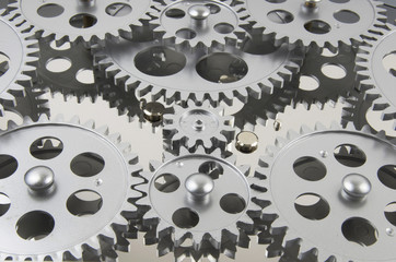 Silver Gears Working Together And Interlocked