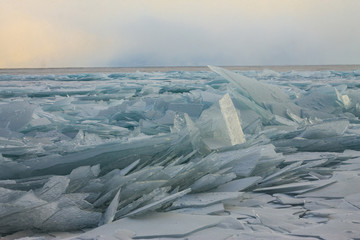 Transparent Baikal ice hummocks at sunset in the fog