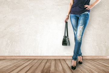 Young fashion woman's legs in jeans and holding bag on wooden fl