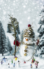 Snowman and people in pine woods during winter