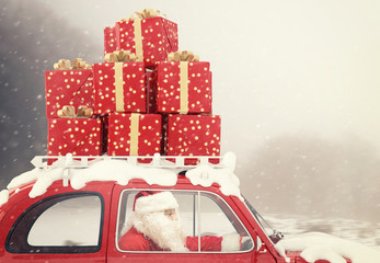 Santa Claus on a red car full of Christmas present