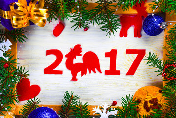 Frame of fir branches and holiday toys with balls on the background of the wooden planks of the new year numbers