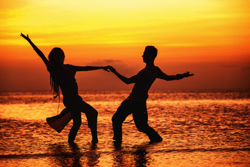 Silhouette of hot dancing couple at golden tropical sea sunset