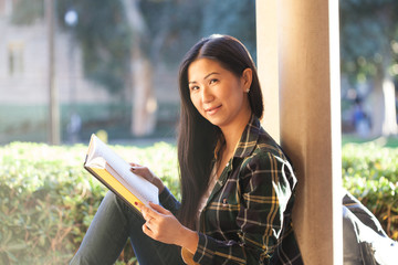 Pretty young Asian girl smiles and looks in the camera, holding