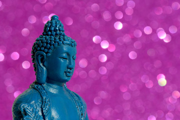 Blue Buddha statue on a bright shiny glitter background with bokeh