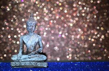 Buddha statue on a bright shiny glitter background with bokeh