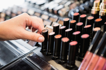 woman chooses lipstick in store