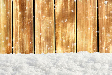Falling snow on a background of an blurred old wooden barn wall