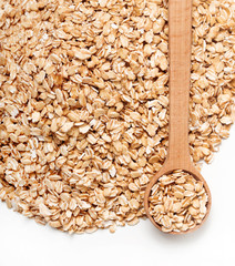Close up heap of oats and spoon on white background. Diet, healthy food. Top view, high resolution product