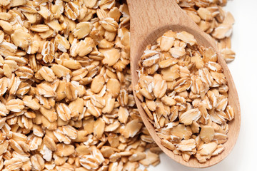 Oat flakes in wooden spoon and on white background. Close up, top view, high resolution product